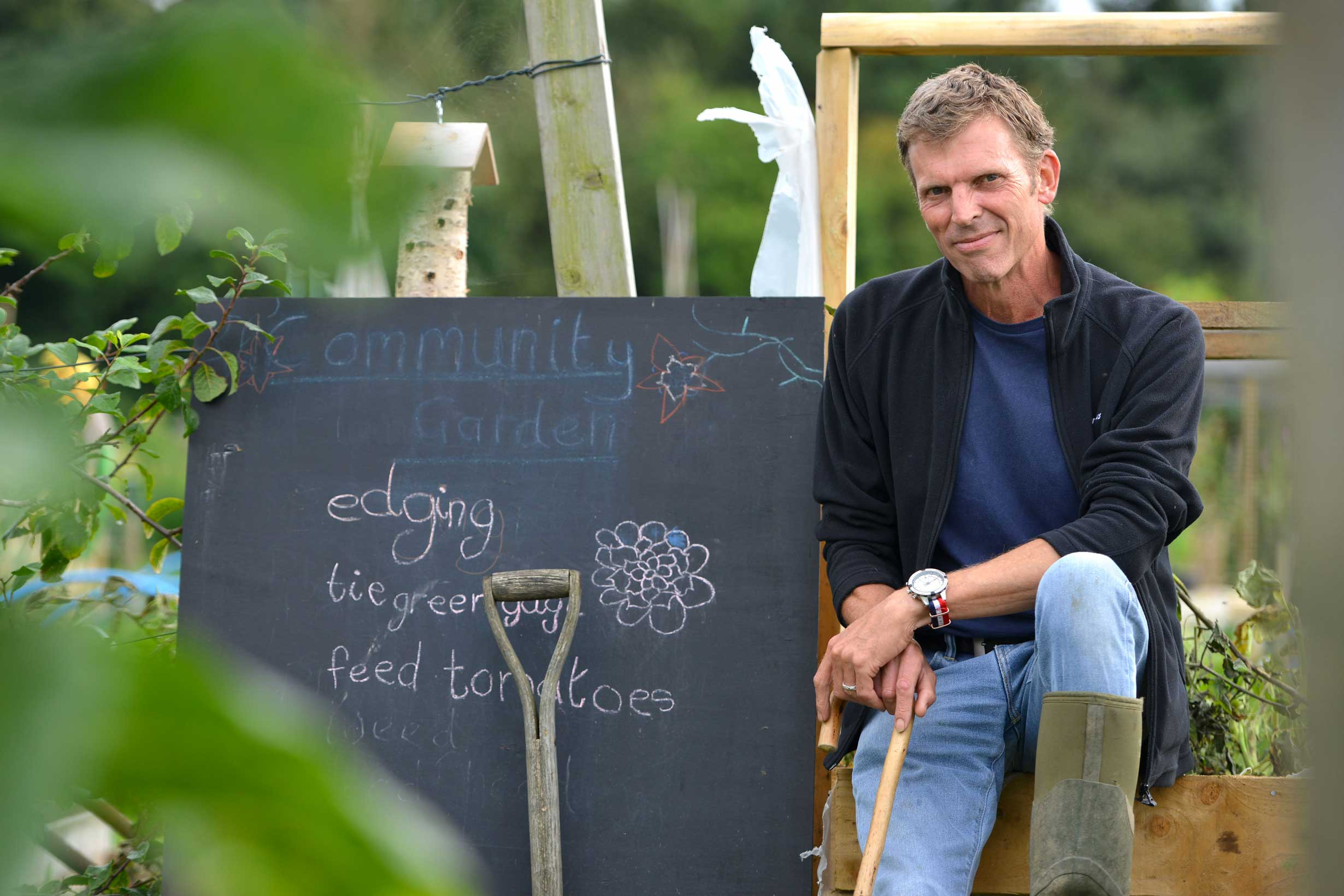 Man at community garden beside the chalkboard notice