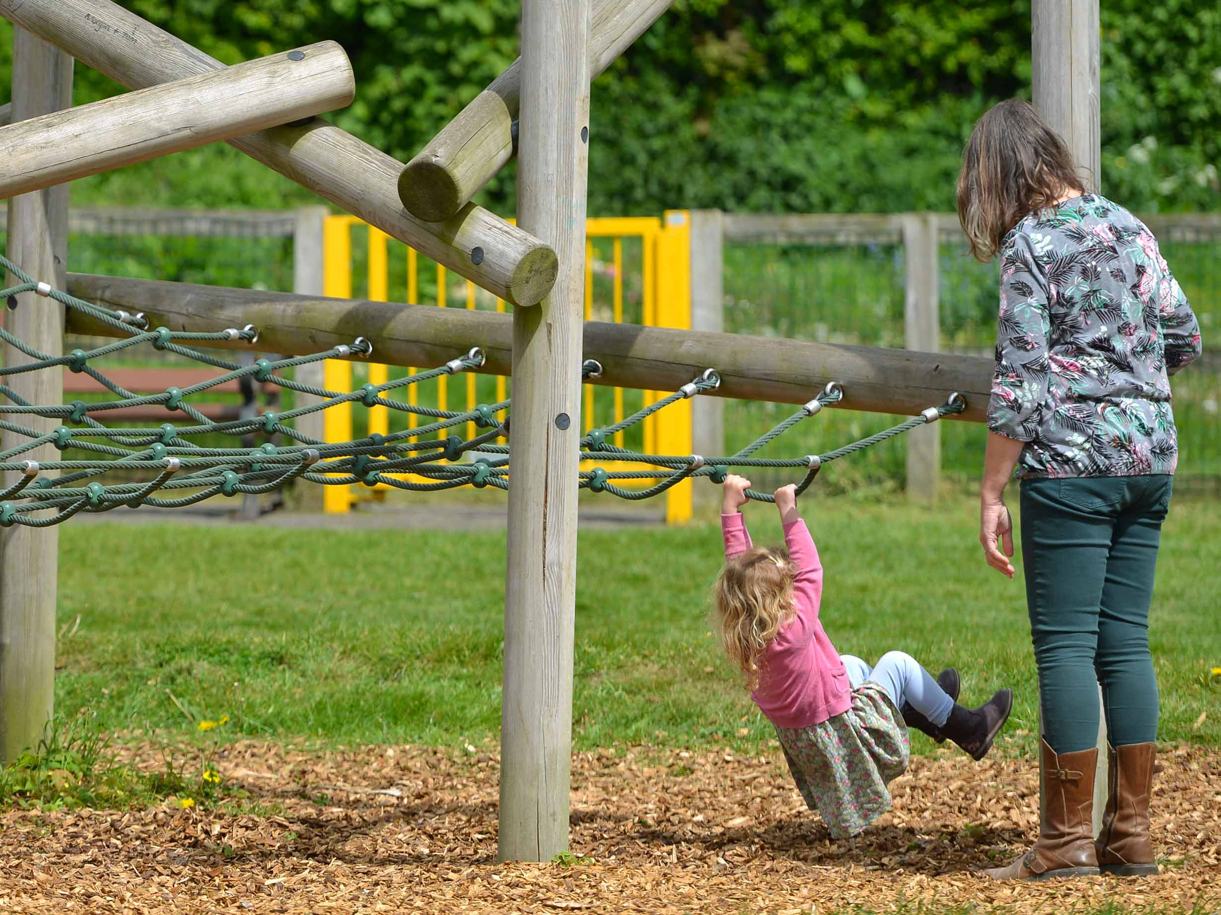 mother and toddler girl playing at play park close up