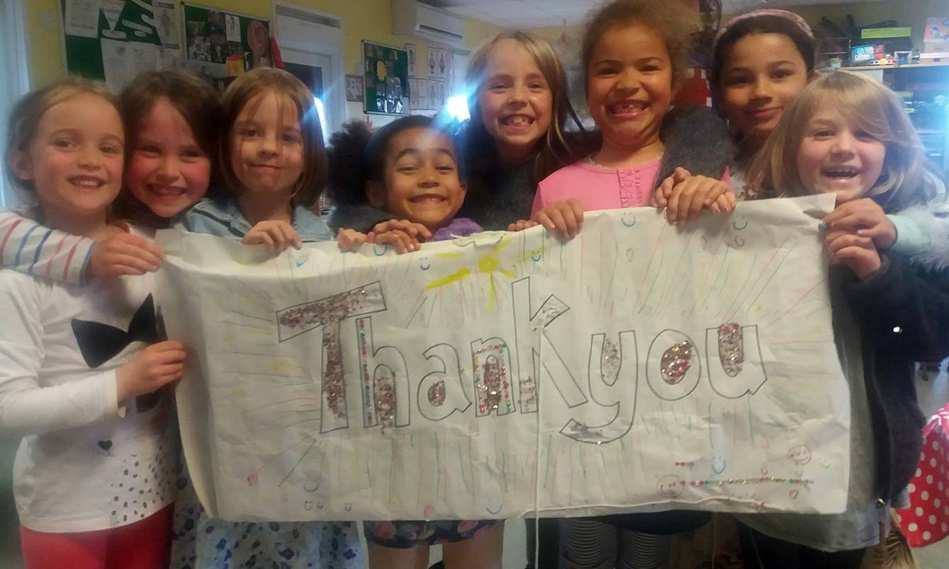 Tarner kids hold up a 'thank you' banner they made